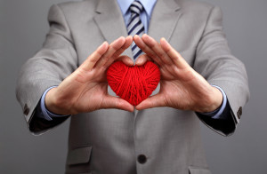 Man holding a red woolen heart concept for valentine's day, business customer care, charity, social and corporate responsibility
